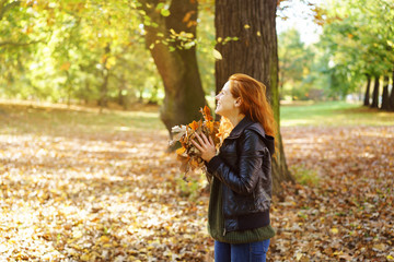 Young happy woman playing with leaves in park