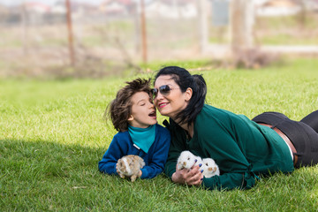 Lovely mother and son with bunnys in grass