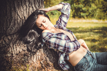 Sexy young woman with sport body in jeans and in a purple plaid shirt posing with at nature, summer sunset. Fashion american style concept