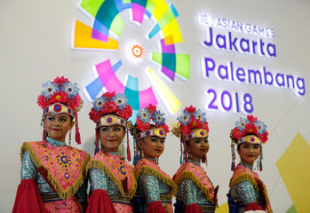 Girls wearing traditional costume stand in front of the logo of the 18th Asian Games at Gelora Bung Karno sports complex in Jakarta