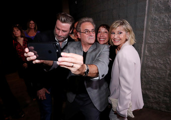 """Cast members Travolta, Pearl, Conn and Newton-John pretend to look away as they pose for a selfie at a 40th anniversary screening of """"Grease"""" at the Academy of Motion Picture Arts and Sciences in Beverly Hills"""