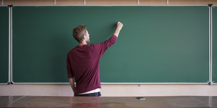 young student in casual writing physics formula on the empty blank blackboard during study course copy space mock up