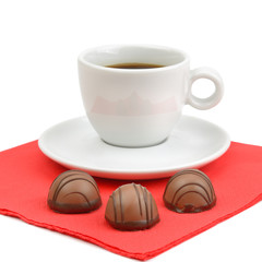 A cup of coffee and chocolate candies isolated on white background.