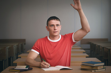 Student is raising his hand and wants to answer the teacher's question.
