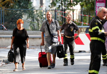 Residents are escorted by firefighters after they recovered their personal belongings from their houses following a Morandi Bridge collapse, in the port city of Genoa