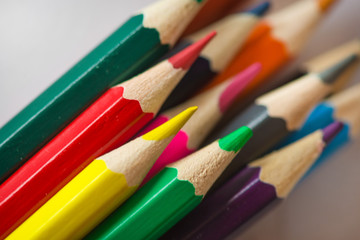 Pile of sharp coloured drawing pencils on table. Rainbow colors  red, yellow, blue, green, purple. Concept of art, crafts and kids having fun