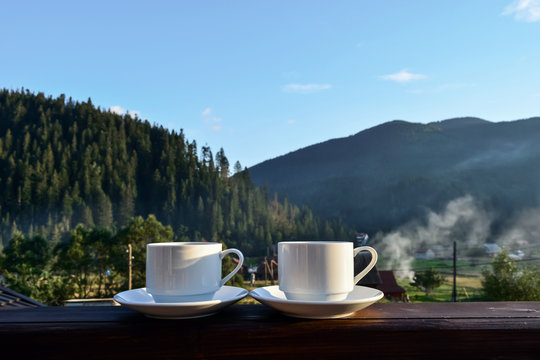 a cup of tea, coffee, standing on the porch of the hotel balcony, overlooking the mountains, in the early morning in the sunlight