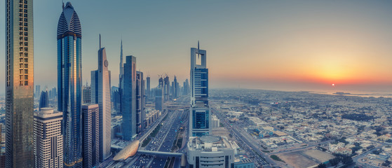 Skyscrapers and highways of a big modern city at sunset. Aerial panoramic view on downtown Dubai, United Arab Emirates.