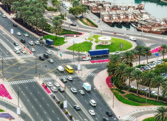 Highways and port in Dubai, UAE. Aerial view of crossroads with city traffic and boats.