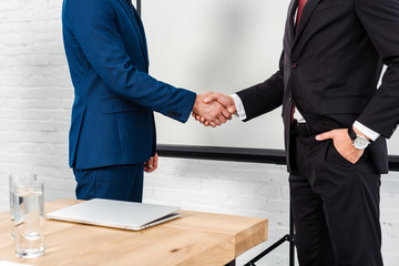 cropped shot of businessmen shaking hands at modern office