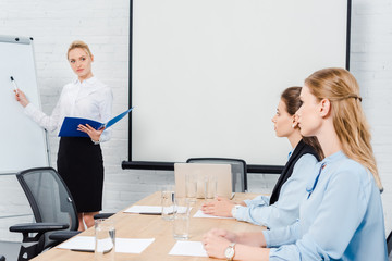 successful lady boss making presentation for employees during conferention