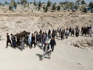 People carry the body of one of the victims of yesterday's suicide attack during a burial ceremony, in Kabul, Afghanistan