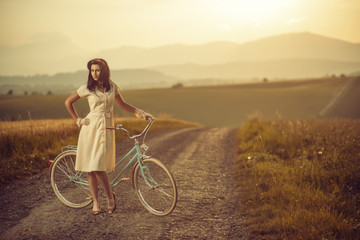 pretty young smilling woman with retro bicycle in sunset on the road, vintage old times, girl in retro style on meadow