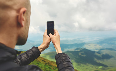 hiker enjoying the view and taking photos by the phone on mountain ridge. Carpathians, Ukraine