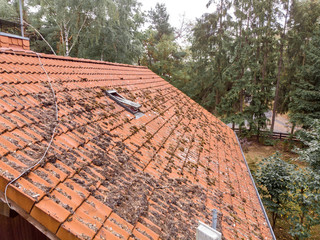 Inspection of the red tiled roof of a single-family house, inspection of the condition of the tiles on one roof side