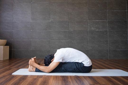 Experienced yogi doing seated forward bend yoga pose in gym. Man practicing yoga. Yogi concept. Side view.