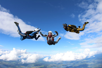 Skydiving. Two instructors are training a student to fly.