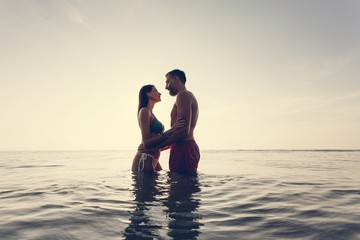 Romantic couple in the sea at sunset