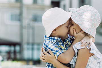 Closeup portrait of little boy and girl embracing and kissing outdoors. Side view.