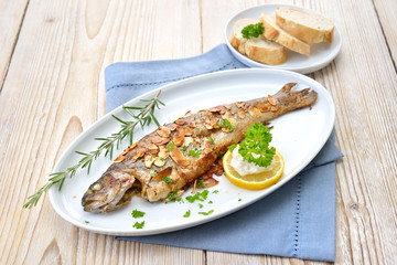 Gebratene Forelle Müllerin Art mit Butter-Mandeln, serviert mit Meerrettich, Zitrone und Baguette  – Fried trout with almonds, butter and creamed horseradish