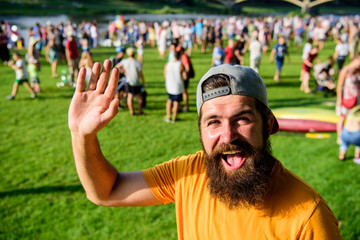 Hipster in cap visiting social event picnic fest or festival. Urban event celebration. Man waving hand sunny day outdoors. Man bearded hipster in front of crowd people green field background