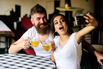 Couple cheerful mood drinking beer in pub. Couple in love on date drinks beer. Take selfie photo to remember great date in pub. Man bearded hipster and girl with beer glass full of craft beer
