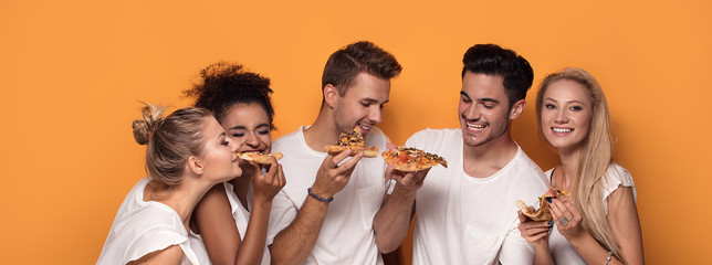Multiracial people having fun, eating pizza.