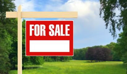 For Sale Schild vor Wiese als Grundstück Konzept