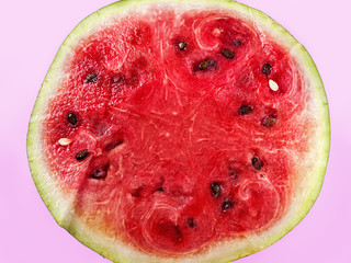 A cut of a whole ripe juicy watermelon on a pale purple background