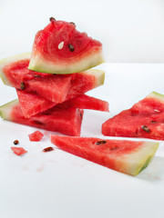 Pieces of ripe juicy fresh watermelon stacked on top of each other on a white background