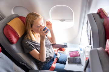 Woman on commercial passengers airplane during flight. Female traveler seated in passanger cabin drinking coffee. Sun shining trough airplane window.
