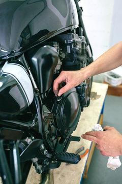 Mechanic repairing customized motorcycle in the workshop