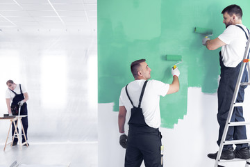 Wall painter on a ladder and a renovation crew worker painting a wall green with rollers and a carpenter in a blurry background in a spacious office interior