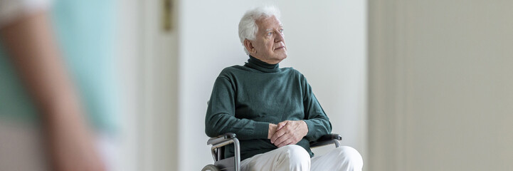 Panorama of disabled elderly man in the wheelchair in a nursing house