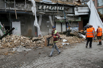 A worker removes debris from a building damaged by a heavy storm in central Kiev