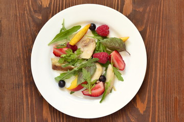 Chicken salad with fresh berries and arugula, top view