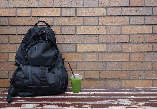 黒いリュックと緑茶 レンガ 休憩 Black backpack and green tea brick break