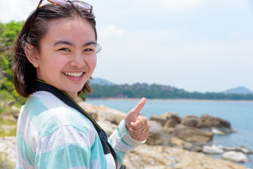 Young woman raised thumb up was happy to photography with dslr camera on the rock near the sea under the summer sky at Koh Samui island, Surat Thani province, Thailand