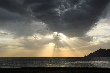 Fotomurales - Dark clouds in front of the sun over the sea. Corsica, France.