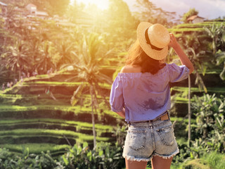 Young woman looking at beautiful tegallalang rice terrace in Bali, Indonesia