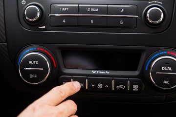 Closeup of a Hand Pressing a Button of a Car Audio System