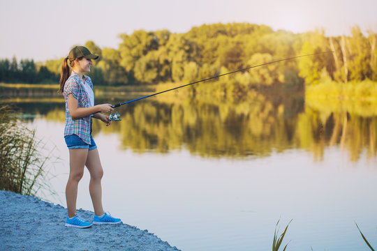 Cute woman is fishing with rod on lake