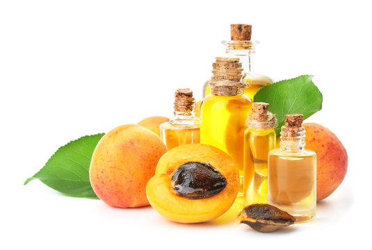 Bottles of apricot essential oil on white background