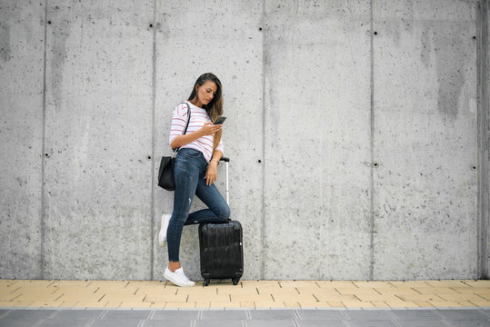 Woman using smart phone while leaning on the luggage on the street.