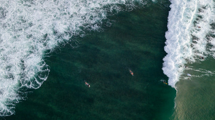 Aerial: Surfers catching the ocean waves