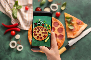 Woman taking photo of tasty Pepperoni pizza on table