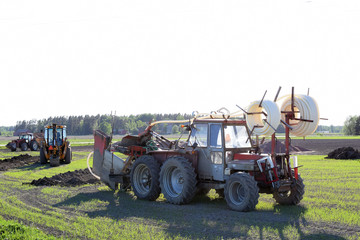 Tractors and excavator on the field making a drainage.