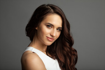 Portrait of beauteous gentle girl with engaging dark brown eyes. Fashionable female with professional natural make-up looking at camera with gladness