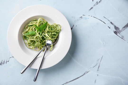 Plate of spaghetti with zucchini and pesto sauce on table
