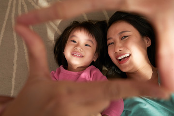 From above shot of happy Asian woman making frame with fingers while lying with charming girl on bed having fun